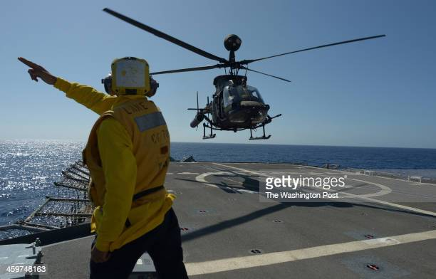 US Army OH58 Kiowa Warrior helicopter maneuvers for touchandgo landings on board the USS Lake Erie CG70 a Ticonderoga class United States Navy guided...