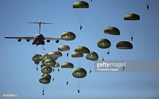 U.S. Army paratroopers jumping out of a C-17 Globemaster III aircraft.