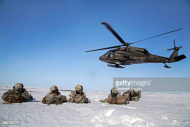U.S. Army paratroopers pull security after exiting a UH-60 Black Hawk.