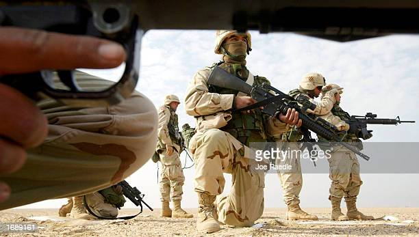 S Army PE2 Carlos Sotomayor from Miami Florida and other Infantry men practice clearing trenches December 16 2002 near the Iraqi border in Kuwait...