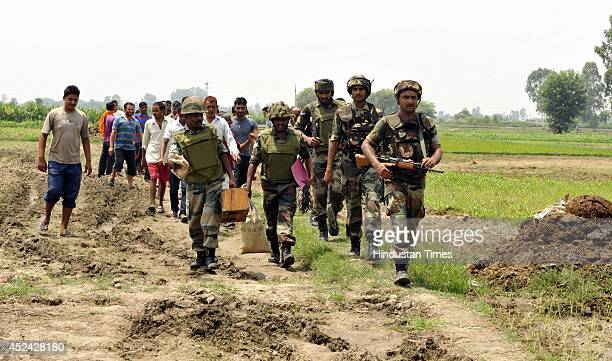 Army personals coming out from a field after defusing mortar shells fired by Pakistani rangers targeting 15 border outposts and several border...