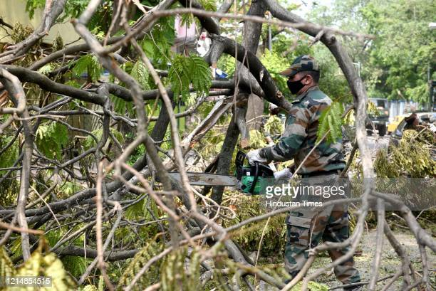 Army personnel clear the streets of uprooted trees after Cyclone Amphan at Southern Avenueon May 24 2020 in Kolkata India Cyclone Amphan made...