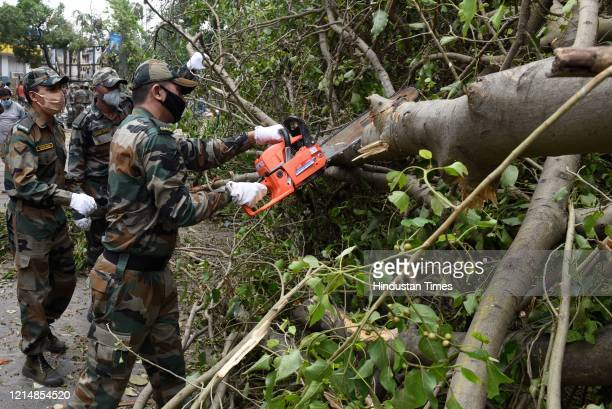 Army personnel cut the branches of an uprooted trees to clear the road blockage after Cyclone Amphan at Southern Avenueon May 24 2020 in Kolkata...