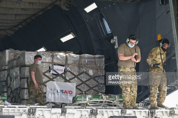 Army personnel prepare to unload Covid-19 coronavirus relief supplies from the US at the Indira Gandhi International Airport cargo terminal in New...