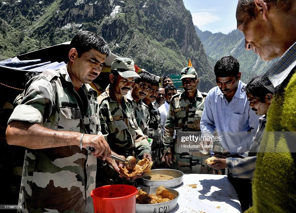 Army personnel serving food to people who are stranded near Govind Ghat for more than two weeks due to land slide at Govind Ghat on June 30 2013 in Uttarakhand, India.