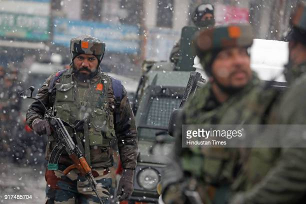 Army personnel take positions during an encounter with the militants who were sheltering in a building near a CRPF camp at Karan Nagar on February 12...