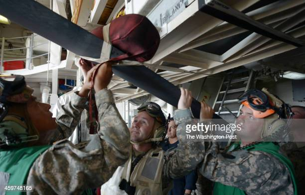 US Army personnel use some tape to secure some padding to prevent damage to the OH58 Kiowa Warrior helicopter blades on board the USS Lake Erie CG70...