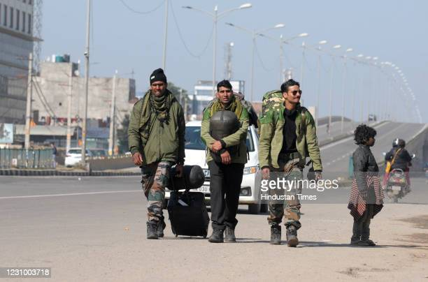 Army personnel walk with their luggage on Zirakpur highway during the pan-India Chakka Jaam called by farmers against the new farm laws, on February...