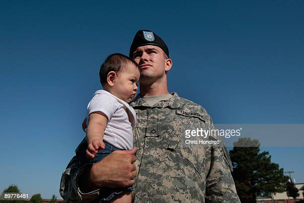 S Army Pfc Wayne Gonzalez of Los Angeles California holds his 8monthold daughter Katelyn during a deployment ceremony as more soldiers at Fort Riley...