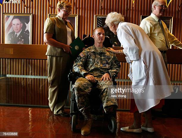 Army Pfc William Goodman of Concord North Carolina is greeted by Red Cross volunteer Lina Czubas as his mother Debbie looks on after a Purple Heart...