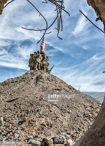WWII US Army Platoon Standing Atop Hill With American Flag