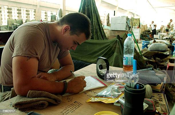 S Army Private 1st Class Nathan Jaques from Las Vegas Nevada writes a letter back home to his family while enjoying a bit of down time at his bunk...