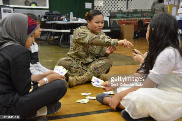 Army Private Jessica Camacho playing cards with children, waiting for treatment during Operation Empower Health at the Garden City Recreational...