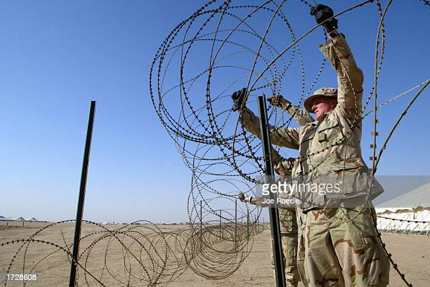 S Army Pvt Delbert Spaur from Colombia Missouri and others put up razor wire at camp New York as they prepare space for troops arriving from America...