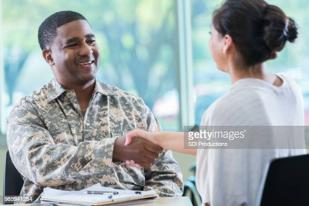 army recruitment officer greets potential recruit - veterans stock photos and pictures