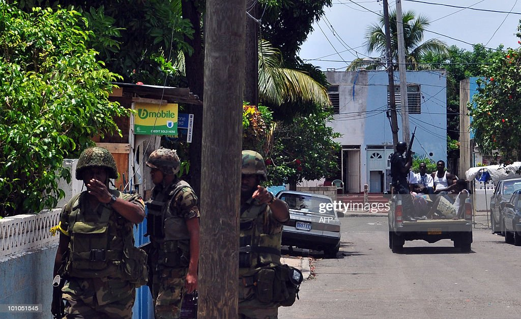 Army reinforcements arrive at the troubled Tivoli Gardens locality of Kingston, Jamaica, where security forces are waging a house-to-house search for a powerful druglord. Heaps of sometimes smoldering garbage littered streets of western Kingston, a world away from Jamaica's famous beaches and the stronghold of gangster Christopher 'Dudus' Coke -- who is wanted by the United States on drug charges. AFP PHOTO / Ratiba HAMZAOUI