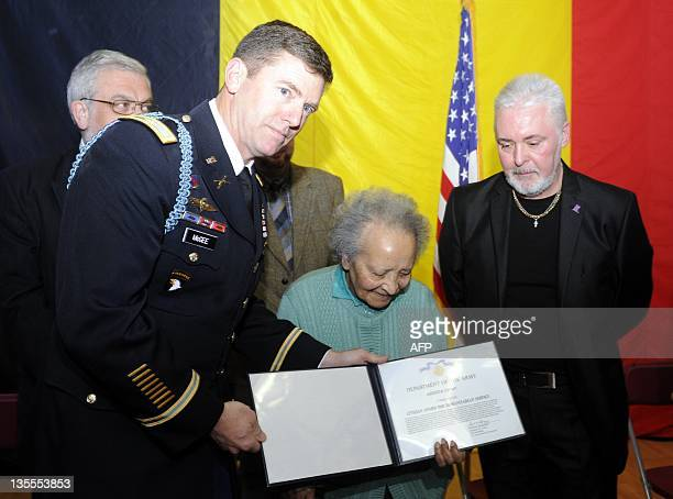 US Army representative Mc Gee Lady Augusta Chiwy and an unidentified man attend on December 12 2011 a ceremony to award her the United States...