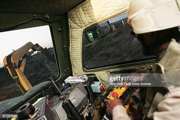 Army Reserve Engineer Sgt Carlos Brown uses a boom rake to search for improvised explosive devices in Baqubah Iraq from aboard a 12foothigh...
