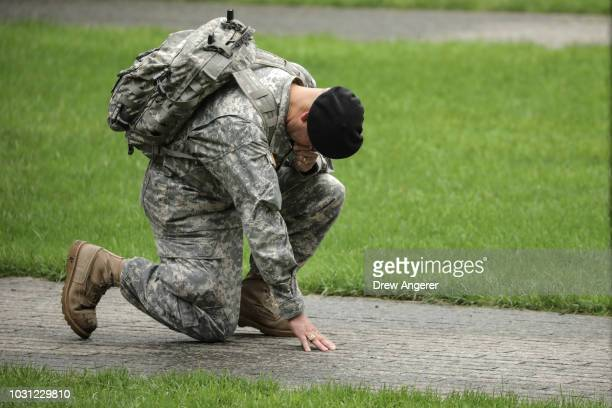 Army Reserve Sgt Edwin Morales kneels in memory of his late friend Ruben Correa a firefighter who died in the 9/11 attacks before the start of a...