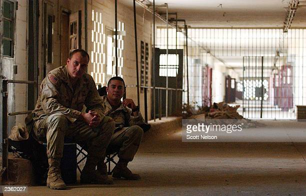 S Army Sergeant 1st Class Gustavo Leigh from Las Vegas Nevada and Sergeant Frank Digiovanni also from Las Vegas supervise Iraqi workers rebuilding a...