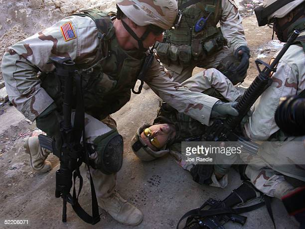 Army Sergeant 1st Class Troy Hawkins of the 1st Cavalry, Task Force 1-9, is tended to after getting wounded during a firefight while on patrol with...