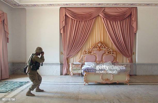 US Army Sergeant Craig Zentkovich from Connecticut belonging to the 1st Brigade Combat Team photographs a pink bedroom at Saddam Hussein's...