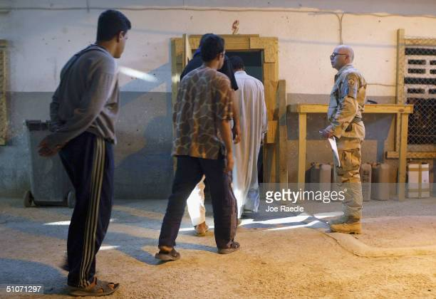 S Army Sergeant Dale Wall from Holland Michigan of the 391st Military Police Battalion watches as prisoners are moved into a cell as they wait to be...