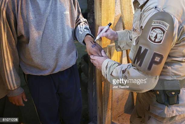 S Army Sergeant Dale Wall from Holland Michigan of the 391st MP battalion marks a prison as they are processed for release from Abu Ghraib prison on...