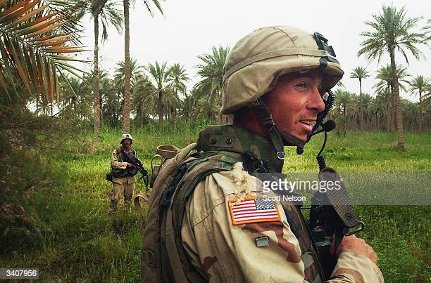 S Army Sergeant David Anderson from Eureka IL leads his 1st Battalion 14th regiment of the 25th Infantry Division squad across an Iraqi palm grove...