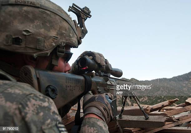 US Army Sergeant Dostal of the 2nd Platoon 212 Infantry Regiment 4th Brigade Combat Team 4th Infantry Division adjusts the scope of his sniper rifle...
