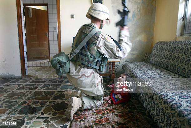 S Army sergeant Lisa Juve from Bismarck North Dakota of the 720 Military Police Battalion attached to the Fourth Infantry Division picks up an Iraqi...