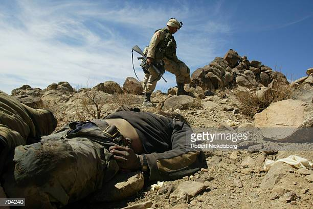 US Army Sergeant Major Dennis Carey of the 10th Mountain Division looks over a dead al Qaeda or Taliban fighter March 16 2002 in the ShahiKot Valley...