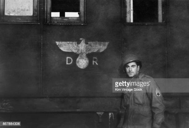 Army sergeant poses next to an abandoned rail road car during the liberation of France The insignia of the socalled 'Deutsche Reichsbahn' the German...