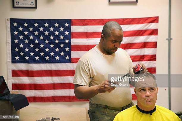S Army SFC Mark Stephens from Philadelphia Pennsylvania gives a haircut to 1SG Donald Lindley from Fayetteville North Carolina during a break from...