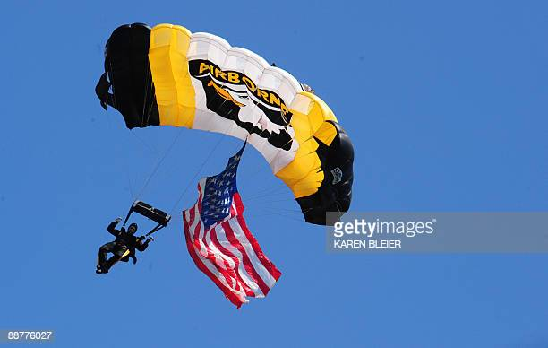 Army Sgt 1st Class Larry Jarrett of the 101st Airborne Division Screaming Eagle Parachute Demonstration Team drops from the sky carrying the US flag...