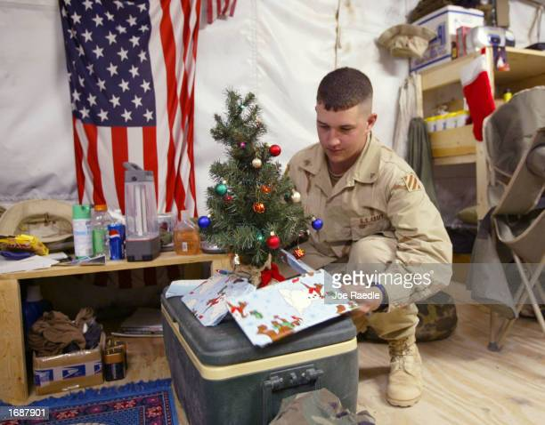S Army Sgt Aaron Lee from Indianapolis Indiana places gifts around a small Christmas tree December 14 2002 in his tent near the border to Iraq in...