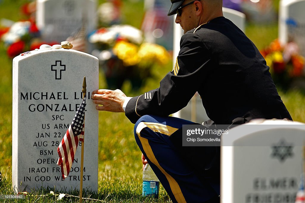 U.S. Army Sgt. Brian Scott touches the grave marker of his friend and gunner Army Specialist Michael Luis Gonzales on Memorial Day in Section 60 of Arlington National Cemetery May 31, 2010 in Arlington, Virginia. Gonzales was killed August 28, 2008, in Iraq by a roadside bomb that severly injured Scott. This is the 142nd Memorial Day observance at the cemetery.