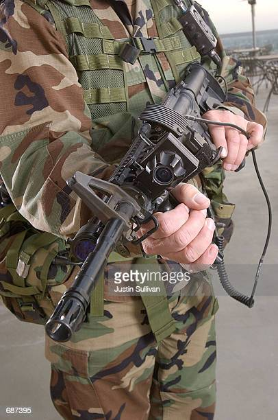 S Army Sgt Chris Augustine displays a M4 Carbine assault rifle as he models the 06 Land Warrior System December 13 2001 at the Homeland Security Expo...