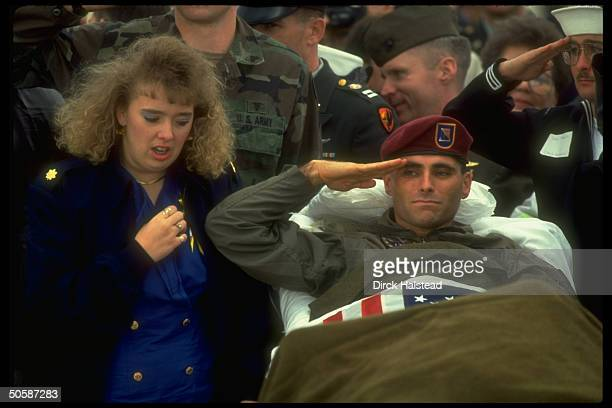 Army Sgt Daniel Stamaris gulf war Iraqiheld POW saluting stretcherbound w broken leg w his wife wellwishers at POWs welcome home ceremony at Andrews...