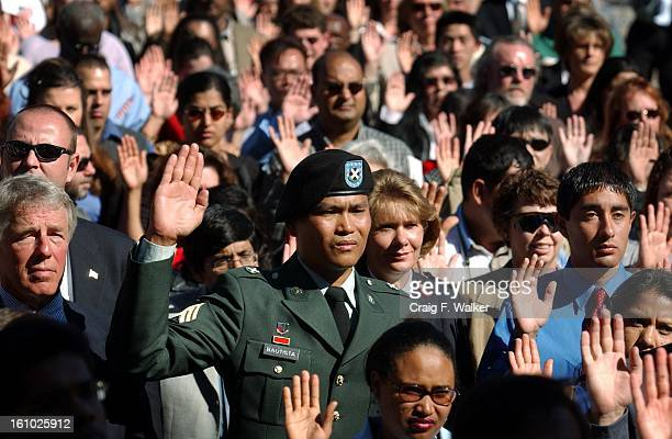 US Army Sgt David Bautista of the Phillipines raises his hand along with close to 600 other new American Citizens as they take their Oath of...