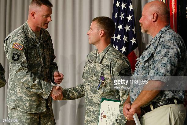 Army Sgt Jeffrey Wray of Chesapeake Virginia shakes hands with Col Terrence McKendrick after he was presented with a Purple Heart during a Purple...
