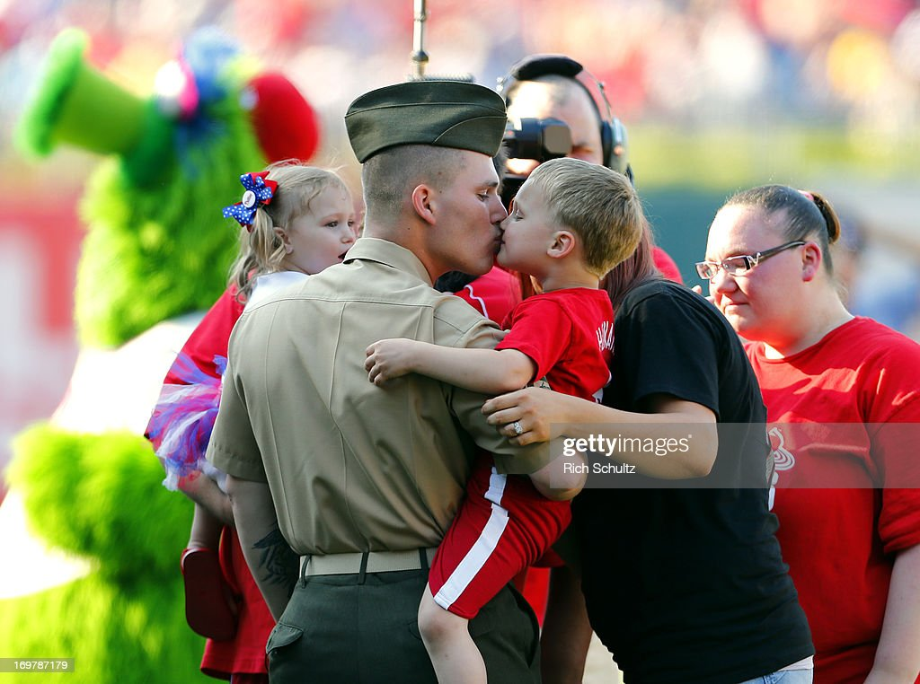 US Army Sgt. Joseph Heim kisses his son Ayden, 4 while his daughter Ella, 2, and wife Katie look on during the fifth inning of a MLB baseball game between the Milwaukee Brewers and the Philadelphia Phillies on June 1, 2013 at Citizens Bank Park in Philadelphia, Pennsylvania. Sgt. Heim surprised his family after being away on a seven month deployment.