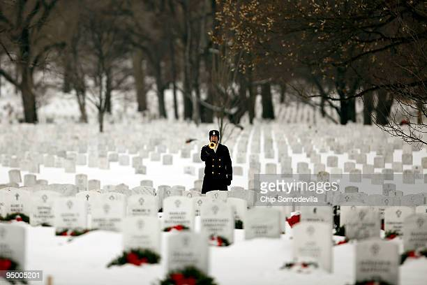 S Army Sgt Maj Dennis Edelbrock plays Taps on the bugle during the burial ceremony for Sergeant Daniel Frazier at Arlington National Cemetery...