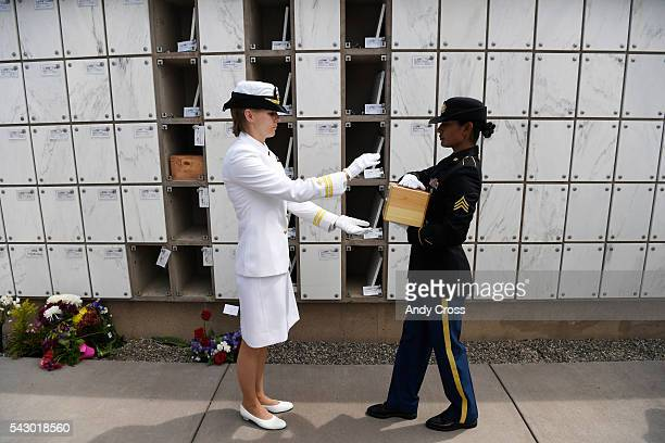 Army Sgt Nisha Ludwig right carries the remains of a Veteran to Navy Lt Jessica Hunt to be interned during a ceremony at Ft Logan June 25 106 Missing...