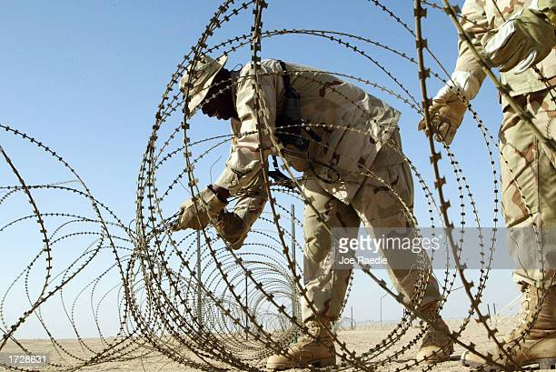 S Army Sgt Oscar DeMoss from Detroit Michigan and others put up razor wire at camp New York as they prepare space for troops arriving from America...