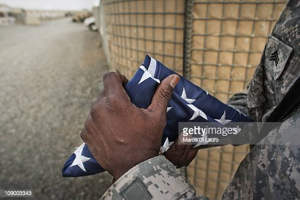 US army SGT Ronald Ross 48 from Georgia Alpha Company 1/121 Infantry 48th BCT folds the US flag after lowering the flag on August 8 2009 in Camp...