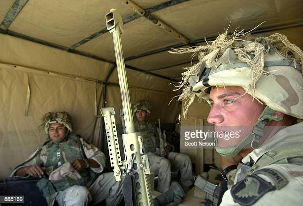 S Army Sgt Tim Gibilisco from Klamath Falls Oregon holds a Barrett 50 caliber sniper rifle as he rides with fellow members of the 3187 battallion of...
