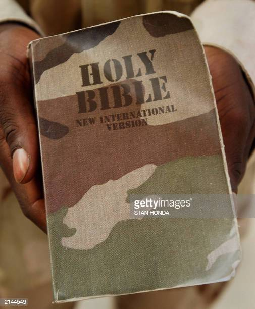 US Army Sgt Towolawi Sikiru of the 137th Armored Division displays his Bible with a camouflage cover after a Sunday evening Christian church service...