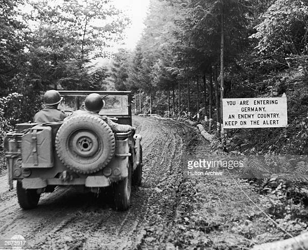 US army signal corps personnel cross the border between Belgium and Germany in a jeep