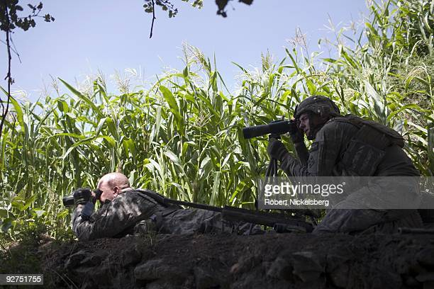 Army sniper left and his spotter right take the range of a Taliban fighter before firing a 308 caliber rifle 1250 meters away during Operation Lethal...